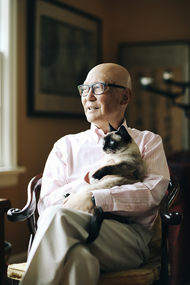 Dr. Ron Naito cuddles his cat, Dolly, at his Portland, Ore., home in May 2019. The poor delivery of Naito's diagnosis with stage 4 pancreatic cancer left him determined to share his experience with future physicians. (Michael Hanson for Kaiser Health News)