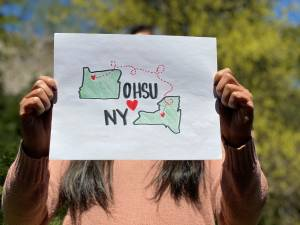 "A person holding up a sign that says ""OHSU hearts NY"" with outlines of Oregon and New York and a line of hearts linking the two."