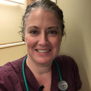 Selfie of a smiling healthcare worker wearing a stethoscope and scrub top