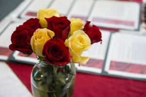 Glass vase with red and yellow roses on a table with framed awards lying on it