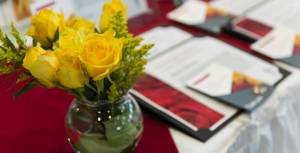 Glass vase of yellow roses on a table with framed awards lying on it