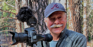 A photo of Gary Albertson outdoors with his photography equipment