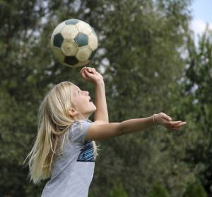 11-year old blond girl playing with a  soccer ball