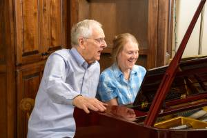 man and woman singing at piano