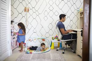 Dad sits working at a desk at home while his baby son and young daughter play in the room behind him