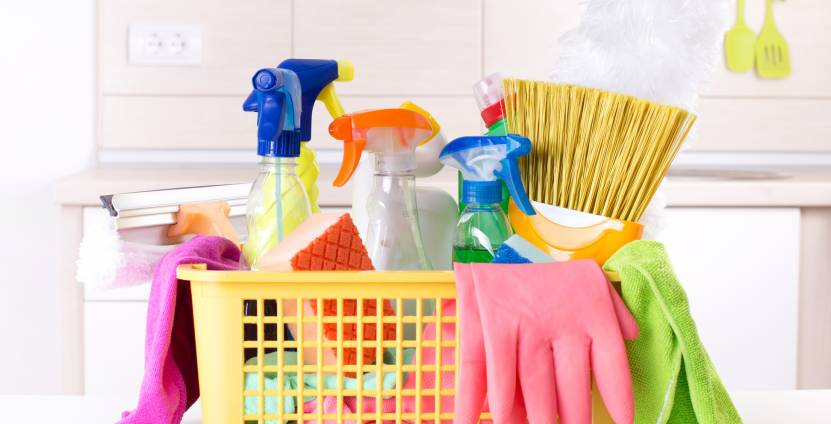 Plastic basket full of cleaning supplies and equipment on white table in front of kitchen cabinets