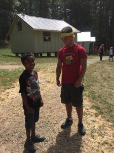 "A child and young adult stand outside, smiling. The young adult is wearing a shirt that says, ""Merry Heart Children's Camp."" In the background are more people and a camp cabin"