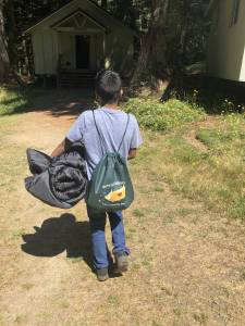 "A child walks toward a camp cabin. He is holding a sleeping bag and wearing a backpack that says ""Merry Heart Children's Camp. Can't Heartly Wait."""
