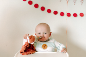A baby in a high chair smiles and holds up a fox blankie. There are balloons tied to his high chair and a decorative banner in the background.