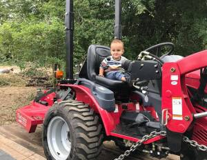 A toddler sits on a red tractor seat. The tractor is on a wooden platform and attached with a chain.