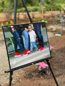 A large photo of four people, including a little boy, wearing red shoes and jeans sits on a display. In the background is a large garden