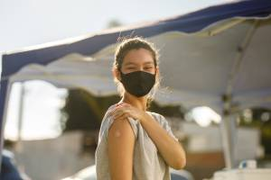 Teenager wearing a mask rolls up sleeve to show a bandage on her upper arm. A large outdoor tent is in the background.