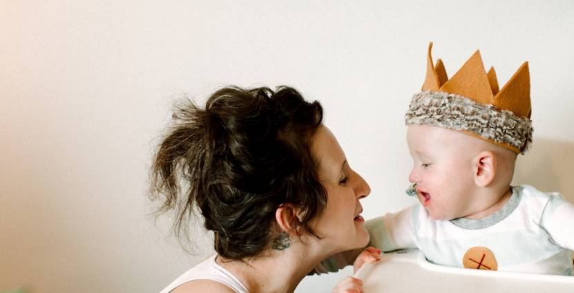 A smiling baby in a high chair wearing a felt crown touches his mom's face as she crouches beside him.