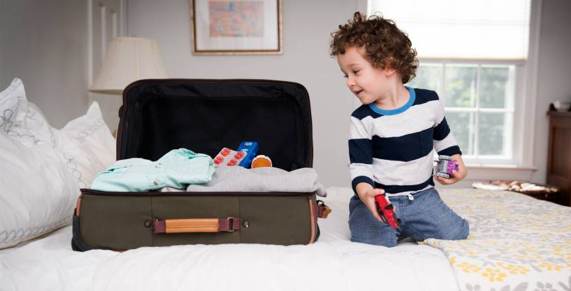 Child kneeling on bed playing with toys and looking inside of an open suitcase with clothes and medications in it