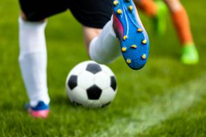 Close-up of young person wearing cleats and shinguards about to kick a soccer ball