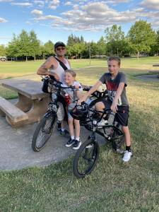 Two children and an adult in a park. Both children are posing with electric bikes.