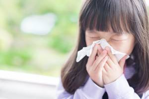 Small child outdoors blowing nose into a tissue