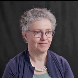Image of Michelle Berlin against a dark background, taken from oral history interview video recording