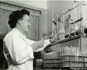 A black-and-white photograph depicts Rose Wong, Ph.D., Research Assistant, working in Biochemistry lab, 1958. She stands facing chemistry lab equipment to the right and smiling in a white lab coat and glasses. In her hand is a pipette.
