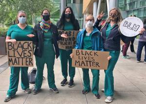 "5 OHSU students pose with signs at a student-led Black Lives Matter Protest on June 13, 2020. Signs read ""Black Lives Matter,"" ""Nursing Students for BLM,"" and ""Defund Police, Fund Health."""