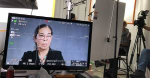 Image showing behind the scenes at the recording of Dr. Lynne Shinto's oral history interview; Shinto's face is shown on a television screen along with the recording studio.