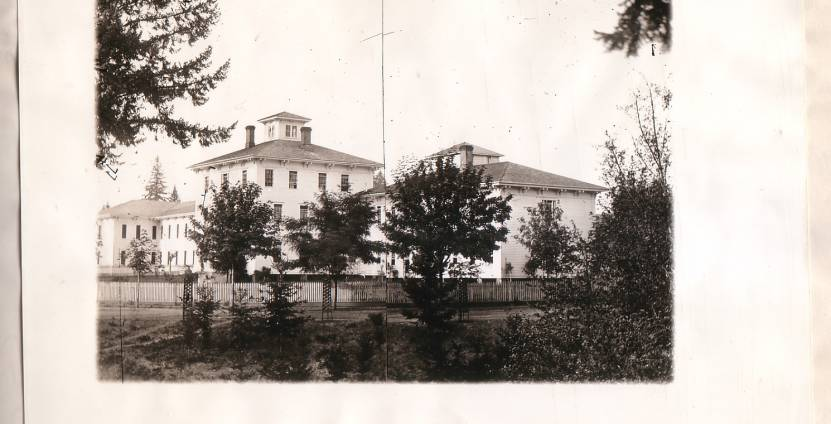 Photo of James C. Hawthorne's asylum. A black and white photograph depicts a large white Victorian hospital building surrounded by trees.
