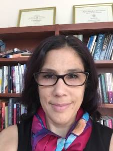Head shot photo of Dr. Dena Hassouneh, standing in front of bookshelves