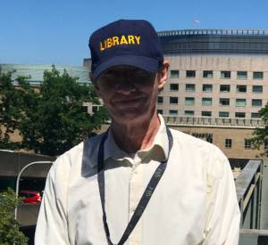 "Jeff Colby stands on the Marquam Hill campus with Kohler Pavilion in the background. He wears a white shirt and a blue hat emblazoned with the word ""Library"""