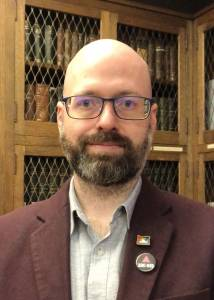 Steve Duckworth is pictured in front of wooden book shelves. He wears glasses, a gray shirt, and maroon blazer.