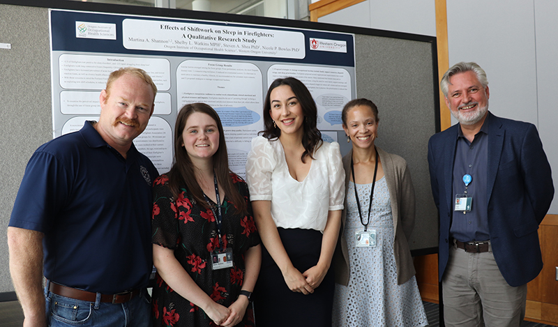 Summer Interns 2019 posing in front of poster with faculty and guest members